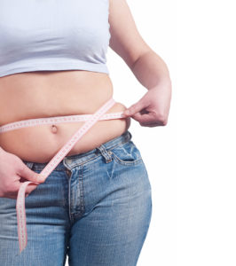 fat woman measuring her stomach to lose weight